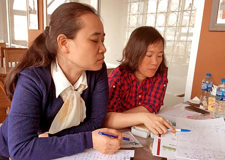 Kaksi aasialaista naista istuu vierekkäin ja tarkastelee työpapereita.
